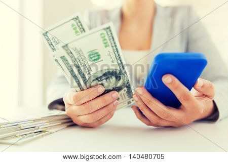 business, finance, saving, technology and people concept - close up of woman hands with smartphone and us dollar money