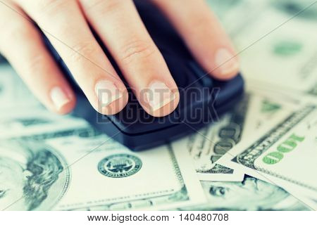 business, finance, internet earning and people concept - close up of hand with computer mouse on money