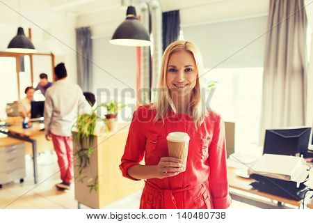 business, startup and people concept - happy businesswoman or creative woman with coffee cup at office