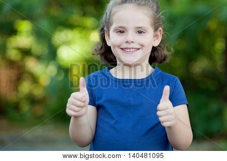 Cute little girl in a summer day saying Ok