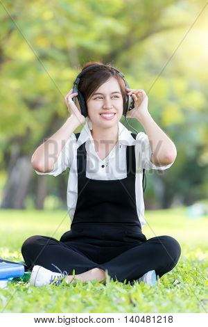 Asian young woman listening music from mp3 player in summer park.Asian young woman look enjoy to listening music.