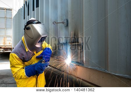 Industry worker with welding steel to repair container structures manufacture workshop in industry factory.