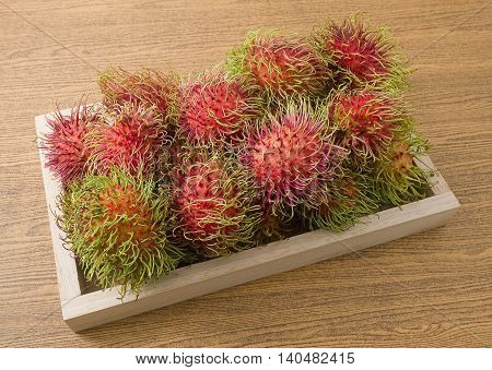 Fresh Fruits Ripe and Sweet Refreshing Rambutan on A Wooden Tray.