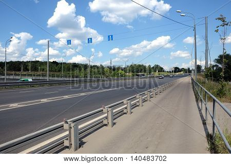 Cityscape with empty urban highway and pedestrian way with fence in sunny summer day horizontal photo side view closeup