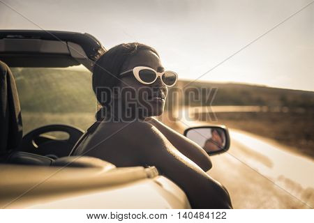 Fashionable woman on a convertible car