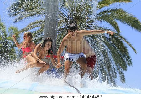 Rhodes Greece-Jun 5 2016:Cheerful group of young people jumping on the wet bubble in the water park .Wet bubble is one of many popular game for adults and children in Water park..Water Park is located in Faliraki on the island of Rhodes in Greece a