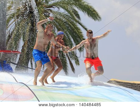 Rhodes Greece-Jun 26 2016:Cheerful group of young people jumping on the wet bubble in the water park .Wet bubble is one of many popular game for adults and children in Water park..Water Park is located in Faliraki on the island of Rhodes in Greece