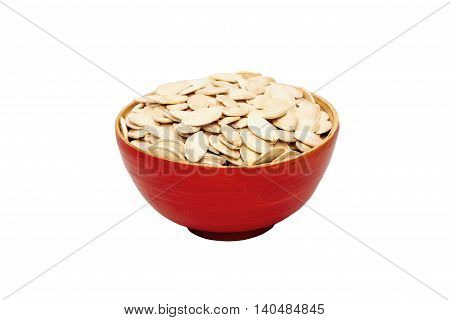 Red bowl with pumpkin seeds  isolated on a white background