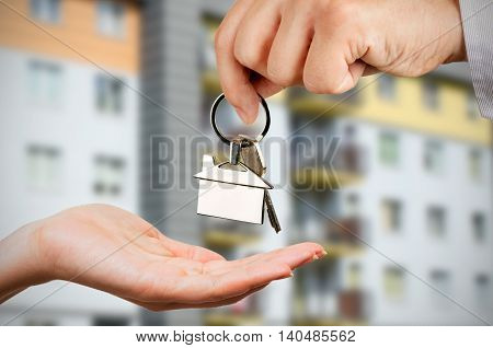 Man gives a woman the keys to a new home. Chrome pedant with house shape