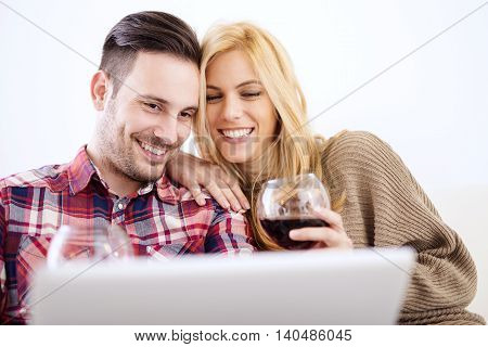 Young couple celebrating with red wine at home.They are sitting close to each other and drinking red wine.