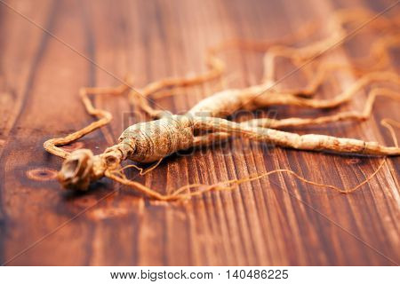 A dry ginseng on the wood background