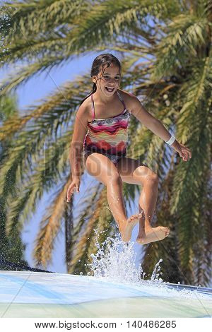 Rhodes Greece-Jun 28 2016:Young girl jumping on the wet bubble in the water park .Wet bubble is one of many popular game for adults and children in Water park..Water Park is located in Faliraki on the island of Rhodes in Greece and one of the most