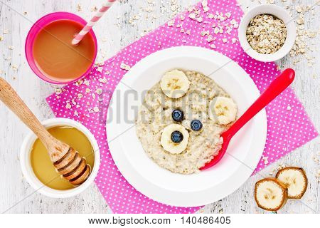 Healthy breakfast for kids - oatmeal with honey banana blueberry and cocoa for drinking. Funny idea for baby food. Edible picture on the plate