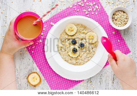Oatmeal porridge with fruit honey and berries - healthy and creative baby breakfast