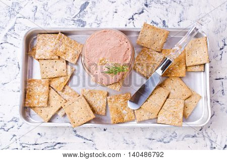Liver pate with crisps on a light background. Selective focus.