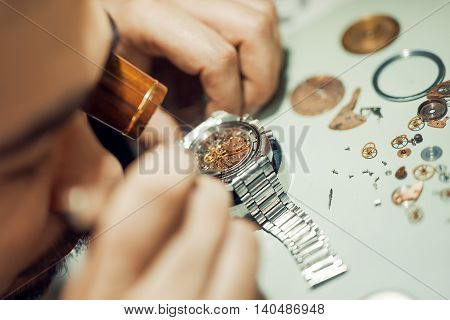 A watchmaker or repair man in actionviewing very closely a watch.