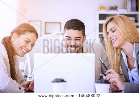 Cropped shot of three business people working on laptop.Three business professionals working together.