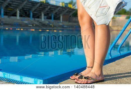 Woman Holding Jeans Pants By The Pool