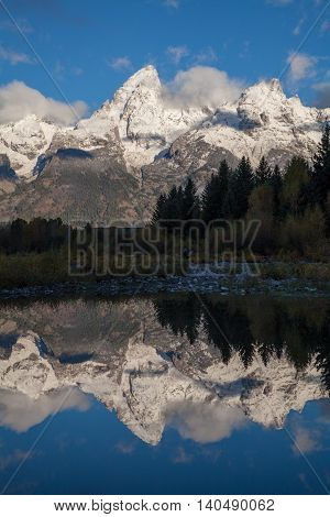 the snow covered tetons in autumn reflected in calm water at sunrise