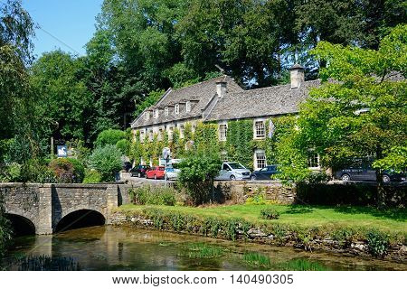 BIBURY, UNITED KINGDOM - JULY 20, 2016 -View along the River Coln towards the stone bridge with The Swan Hotel to the rear Bibury Cotswolds Gloucestershire England UK Western Europe, July 20, 2016.