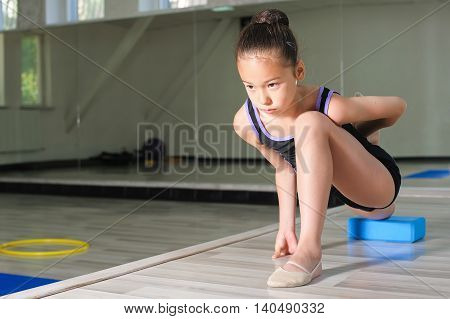 Stretching Little japanese Girl. Attractive beautiful Asian girl doing gymnastics exercises in hall rhythmic gymnastics.