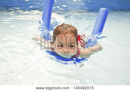 The little girl swims in the pool on vacation