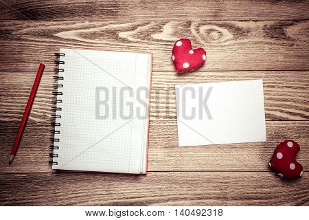 Hearts and notepad sheet of blank paper on wooden table