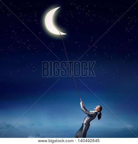 Young woman in suit holding moon planet on lead