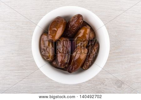 Dried Dates In Glass Bowl On Wooden Table