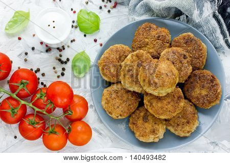 Fried cutlets on a white table with tomatoes and spices top view