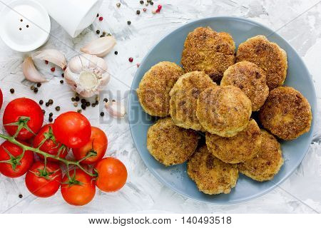 Delicious fried cutlets on the kitchen table with cherry tomatoes garlic and pepper top view