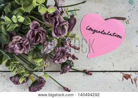Congratulation note in heart shape paper with purple bouquet on grungy white wooden table vintage style