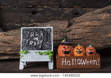 Three pumpkins in the box with trick or treat board on grunge wooden background