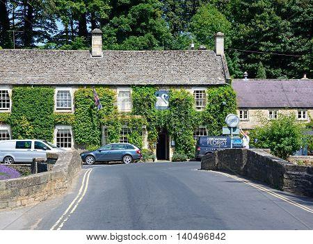 BIBURY, UNITED KINGDOM - JULY 20, 2016 - View across the road bridge towards The Swan Hotel Bibury Cotswolds Gloucestershire England UK Western Europe, July 20, 2016.