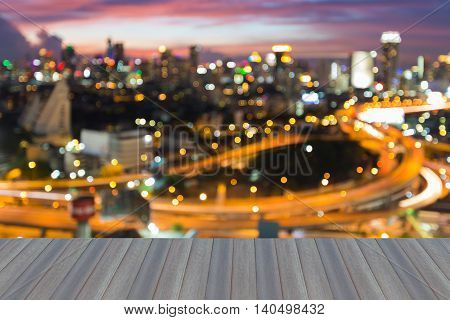 Opening wooden floor, Blurred bokeh lights city interchanged and city downtown background night view