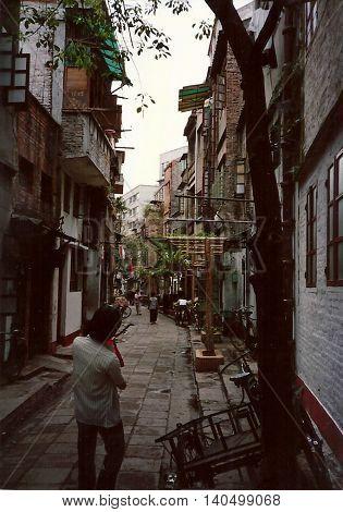GUANGZHOU / CHINA - CIRCA 1987: People walk through a narrow street in Guangzhou.