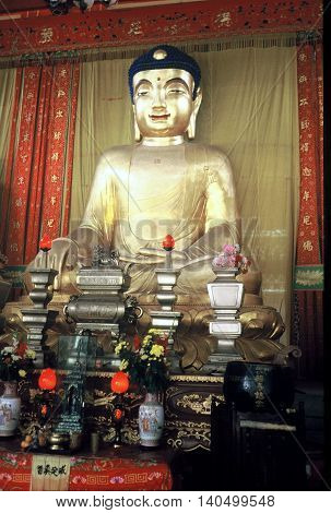 GUANGZHOU / CHINA - CIRCA 1987: An image of the Buddha sits on an altar at the Temple of the Six Banyan Trees in Guangzhou.
