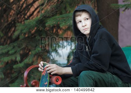 Portrait of resting teenage boy is holding skateboard and sitting on park bench