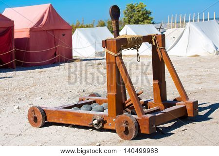 ancient Roman catapult with cannonballs in a military camp