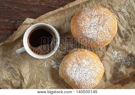 Cup of hot coffee and donuts with powdered sugar on crumpled paper top view