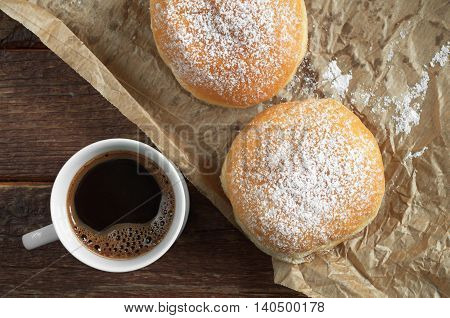 Cup of hot coffee and two donuts with powdered sugar on crumpled paper top view