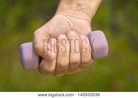 hand holding dumbbell on green blurred background