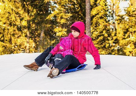 Mother and daughter having fun in the winter riding with snowy mountains on a sled