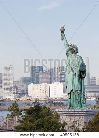 Tokyo - 4 February 2015: Women's figure of the Statue of Liberty with torch in the background of the urban landscape of Tokyo Bay on 4 February 2015 in Tokyo Japan