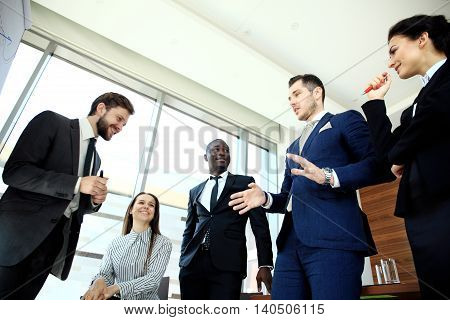 Time to discuss our business plans. Young handsome man gesturing and discussing something while his coworkers listening to him at the office