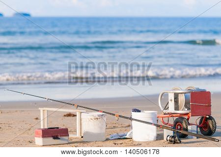 Surf casting fishing rod long-line and buckets on beach