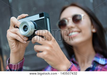 Pretty girl taking photos outdoors. She is standing and smiling. Focus on retro camera