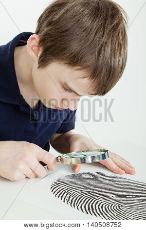Boy Examining Finger Print With Magnifying Glass