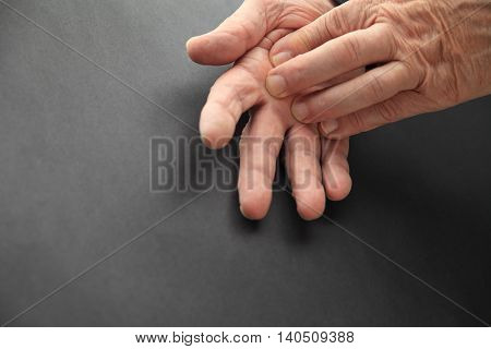 Senior man touches sore area of his hand.
