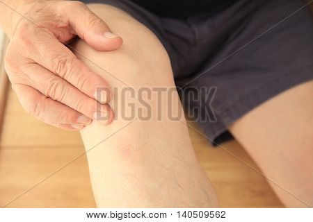 Older man puts a hand on his sore knee joint.